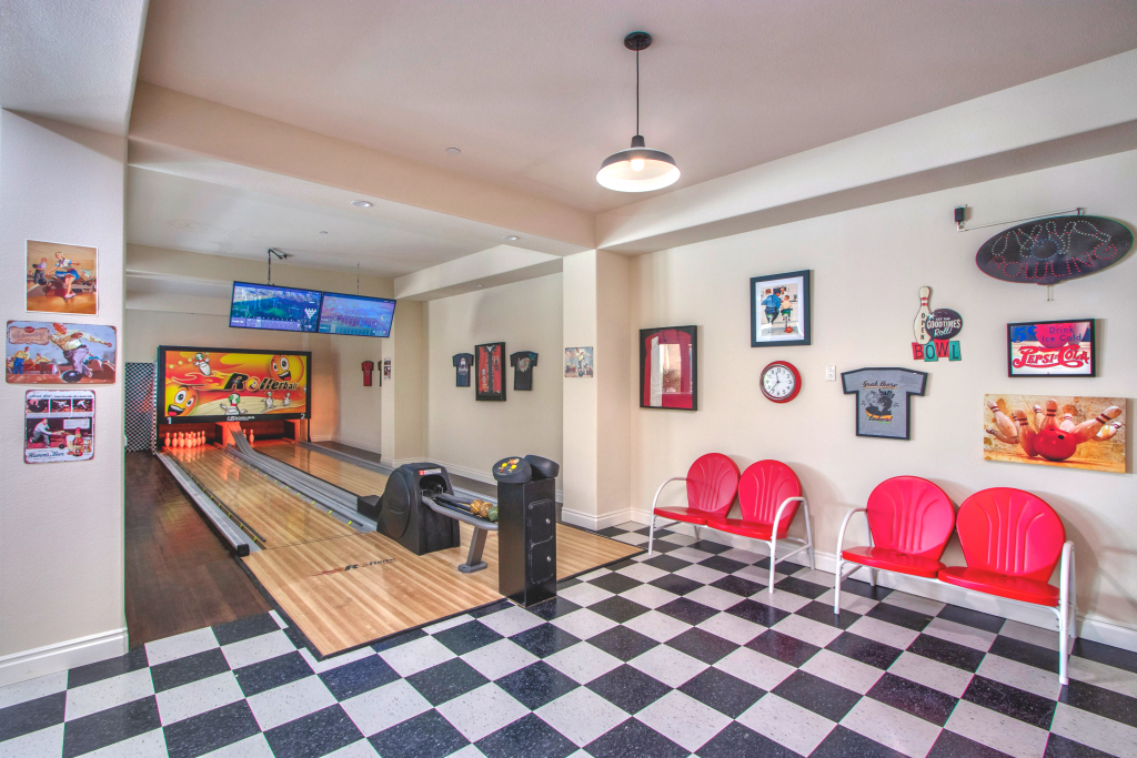 A '50s style bowling alley with checkered floors, bright red seats, and a custom bowling alley