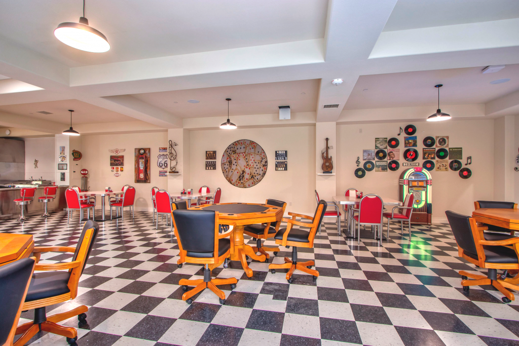 A '50s inspired dining area with black and white checkered floors, game tables, and a jukebox in the back