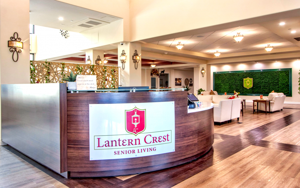 """A large wraparound desk that reads """"Lantern Crest Senior Living"""" with seating and a moss wall to the left"""