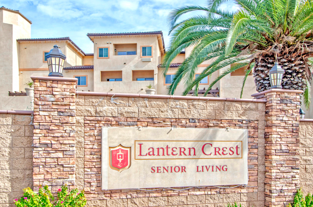 """An outdoor sign made of stone that reads """"Lantern Crest Senior Living"""" There are tan buildings and a palm tree behind the sign."""