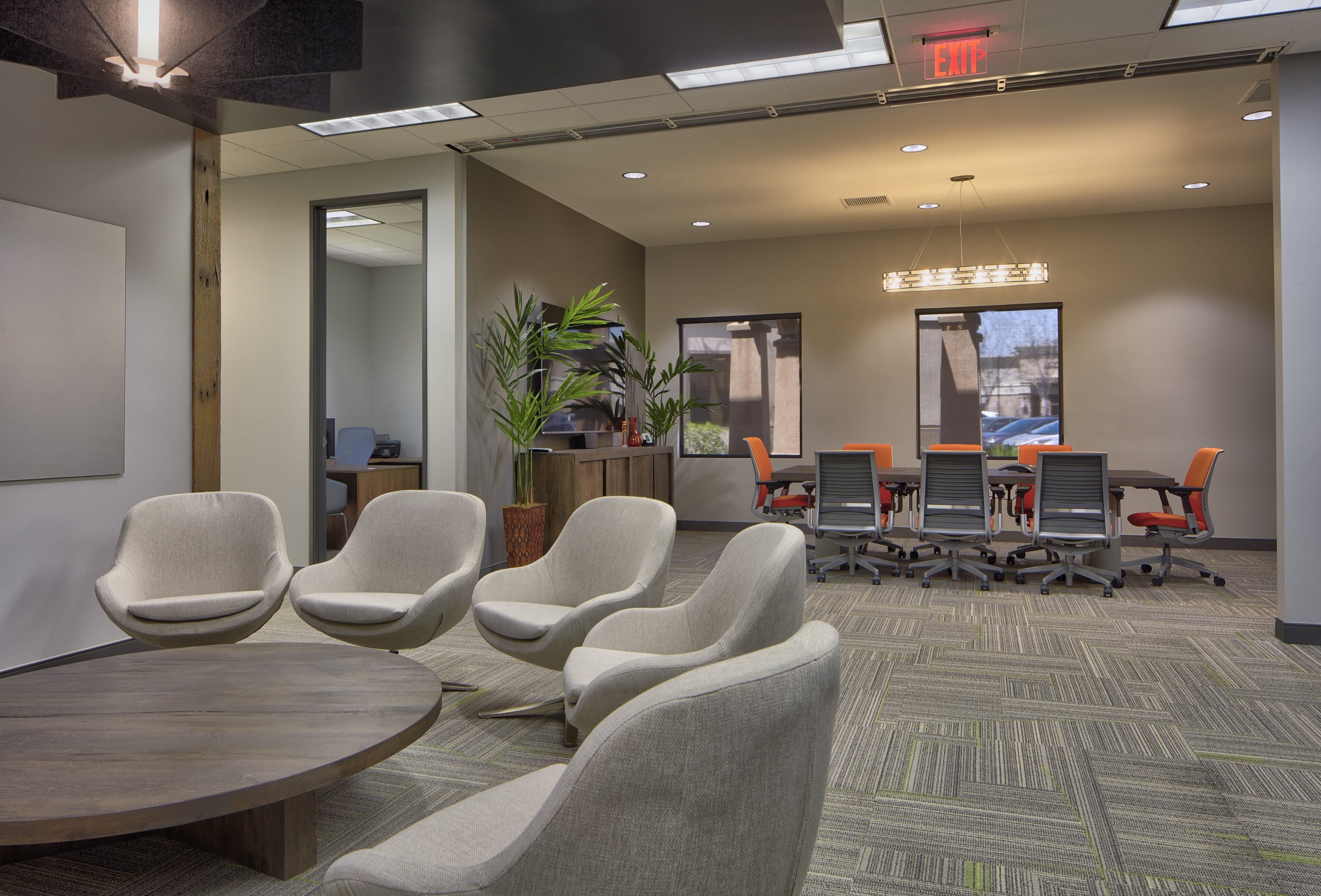 A coworking area with gray chairs in a circle. Behind the chairs, you can see a conference room.