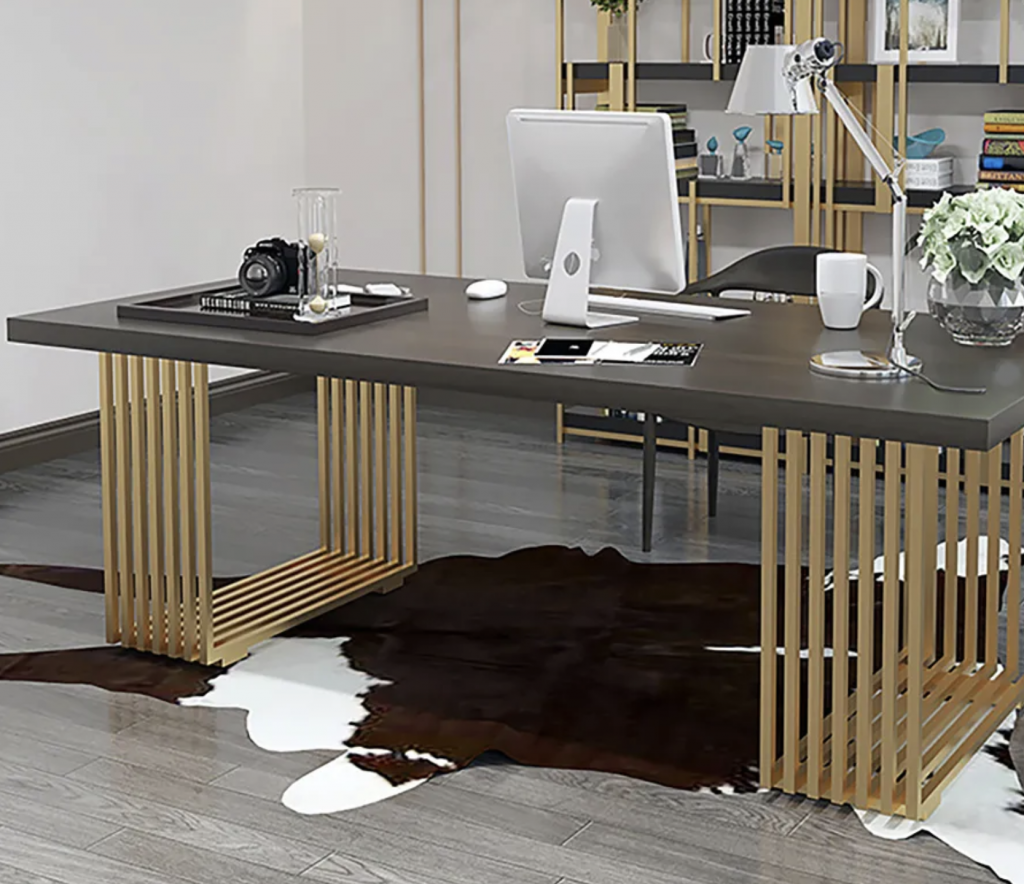 An executive office with a black topped desk that has several gold legs