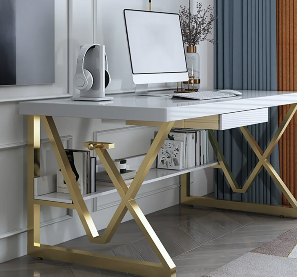 A work from home office with a white marble desk and gold intricate legs